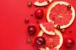 Leinwandbild Motiv Slices of ripe grapefruit, plums and grapes on color background