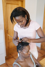 Woman Fixing And Combing Her Sister Head While Making Braiding Her Hair At Home. Hair Care Concept.