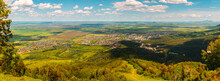 Panorama Of The Village In The Valley. View From The Mountain To The Village At The Foot. Nice View From Height Of City In The Lowlands. Landscape On Sunny Summer Day On The Background Of Blue Sky