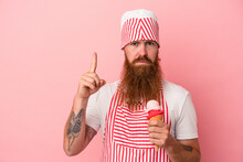 Young Caucasian Ginger Man With Long Beard Holding An Ice Cream Isolated On Pink Background Showing Number One With Finger.