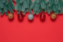 Border From Decorative Spruce Branches With Christmas Balls On A Red Textured Paper Background. Top View, Flat Lay, Copy Space.
