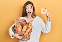 Young Caucasian Girl Holding Wicker Basket With Bread And Loaf With Heart Shape Angry And Mad Screaming Frustrated And Furious, Shouting With Anger Looking Up.