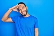 Leinwandbild Motiv Hispanic man with beard wearing casual blue t shirt very happy and smiling looking far away with hand over head. searching concept.