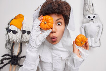 Surprised Woman Covers Eye With Orange Pumpkin Cannot Believe Her Eyes Dressed In Scarying Costume Prepares Decorations For Halloween Isolated Over White Background. Spooky Holiday Is Almost There