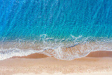 Top View Aerial Drone Photo Of Perissa Beach With Beautiful Turquoise Water And Sea Waves. Vacation Travel Background. Aegean Sea, Santorini Island, Greece