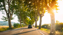 Peyrolles-en-Provence, France. Car In Motion On A Country Road Lined With Trees. Bright Sunlight At Sunset In Evening. French Road Trip Landscape