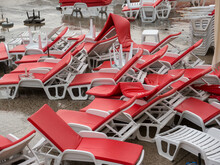 Heap Of White Plastic Chaise Lounge With Red Mattresses And Sunshades On Sea Side Cement Beach Top View