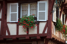 Closeup Of Red Geraniums At He Window Of A Medieval House Facade