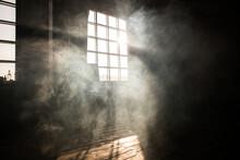 Sunshine Window Reflection On The Wooden Floor. Heavy Smoke In Loft Design Studio. Cinematic Photo.
