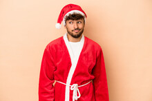 Young Arab Man Disguised As Santa Claus Isolated On Beige Background Confused, Feels Doubtful And Unsure.