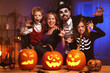 canvas print picture - Young caucasian family mother father and children in Halloween costumes and makeup making scary gesture, saying trick or treat while celebrating together all hallows eve in dark room at home