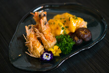 Two Shrimps In Batter With Sauce And Mushrooms On The Blue Designed Plate. Deep Fried Prawns Decorated With Greenery And Flower. Isolated On Black