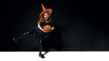 Joyful Girl In Witch Costume Stands On One Leg And Holds Pumpkin