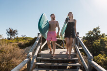 Surfers Walking On Boardwalk Near Plants