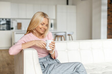 Enchanting Middle-aged Woman Sits On The Couch And Relaxing With A Mug Of Coffee. A Portrait Of Charming Blonde Woman Daydreaming At Home