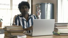 Handsome Indian Male Man Student Using Laptop Then Looking At Camera. Boy Study Remote Or Work In The Kitchen At Home. Stylish Freelancer Asian Man