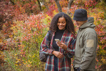 Cropped Image Of Young Beautiful Couple Looking On Photos On Phone Isolated Over Colorful Autumn Landscape. Couple Doing Hiking On Warm Fall Day