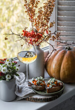Glass Of White Wine And Pumpkin Gorgonzola Bruschetta On The Windowsill. Autumn Still Life With Chrysanthemums, Pumpkin On The Background Of The Window. Autumn Mood