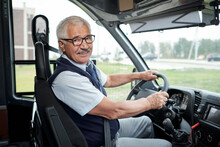 Happy Aged Driver Of Intercity Bus Holding By Steering Wheel During Ride To Another City Or Town