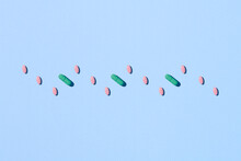 Medicine Concept. Multiple Long And Oval Pink Capsule And Hard Pills On A Blue.