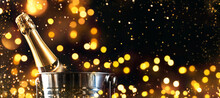 Champagne Bottle In Silver Bucket On Black Background. Happy New Year Or Merry Christmas Composition With Golden Sparkles And Bokeh Lights