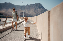 Playful Boy With Mother On Bridge