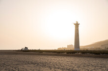 Sandy Beach With White Lighthouse At Sunset