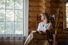 A Beautiful Blonde Woman In Beige Home Clothes Sits In A Cozy Rocking Chair And Reads A Book. Cozy Village Life. Room With Large Windows And Log Wooden Walls.