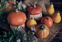 Pumpkins And A Bouquet Of Wildflowers Lie On Rough Burlap On A Wooden Background.