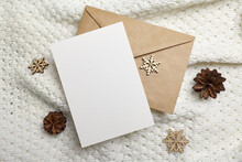 Christmas Greeting Card Mockup With Envelope, Wooden Snowflakes Decorations And Pine Cones On Knitted Background