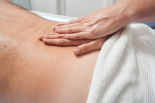 Masseuse Hands Massaging Male Back In Spa Salon