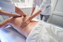 Two Masseuses Massaging Man Back At Wellness Center