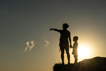 Mother And Son Against The Light Silhouetted By The Sun Pointing With Their Arms Towards The Horizon At Sunset