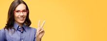 Happy Smiling Business Woman In Red Eye Glasses Showing Two Fingers Or Victory Hand Sign Gesture, Isolated Over Orange Yellow Background. Cheerful Businesswoman Portrait.