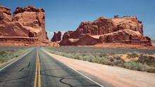On A Road Approaching Red Sandstone Cliffs In Arches National Park, Utah, USA.