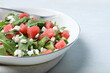 Leinwandbild Motiv Delicious salad with watermelon, cucumber, arugula and feta cheese on white table, closeup. Space for text