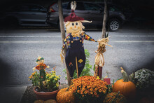 Funny And Smiley Scarecrow With Corn, Plants And Pumpkins On A Wooden Pole
