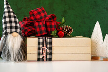Christmas Holiday On-trend Farmhouse Aesthetic Stack Of Books Close Up Styled With Red And Black Plaid Ribbon Bow, White Tree Ornaments And Gnome.