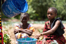 Two Little Black African Girls Crouched Down At The Village Well Waiting For Their Bucket To Be Filled With Clean Drinking Water