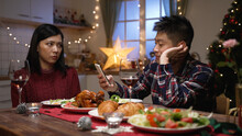 Asian Man Addictive To Phone Is Ignoring His Girlfriend Who's Staring At Him And Cutting Food In Plate With Anger While They Are Having Christmas Dinner At Home