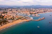 Picturesque Aerial View Of Coastal Area Of Frejus Overlooking Marina With Moored Pleasure Yachts And Residential Districts Along Waterfront In Warm Autumn Day, France