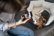A girl making photos of a puppy on her smartphone