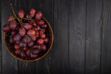 Top View Of A Bunch Of Fresh Sweet Grapes In A Wicker Basket On Dark Wooden Background With Copy Space