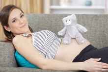Young Pregnant Woman Laying On The Sofa With The Teddy