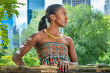 Dressing In A Strapless Colorful Dress, Wearing A Golden Neck Ring, A Pretty Black Woman With Ponytail Hair Is Standing At Small Woods Inside A Big City, Looking Around, Waiting For You..