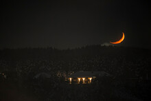 Waxing Crescent Moon Over A Forest. Dark Wintry Sky, Black Woodland Silhouette, Home Building With The Lights On. Selective Focus On The Details, Blurred Background.