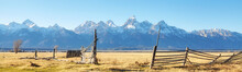 Old Broken Wooden Fence On A Field With Teton Mountain Range In Background, Wyoming, USA.