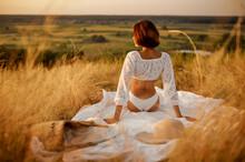 Woman In White Lingerie On Blanket In The Field