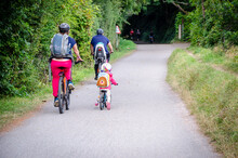 Caucasian Family Of Two Adults And A Child Riding Bikes On Camel Trail In Cornwall From Widebridge Towards Padstow, England, UK