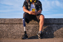 Anonymous Man With Leg Prosthesis Sitting On Stone Barrier And Using Smartphone